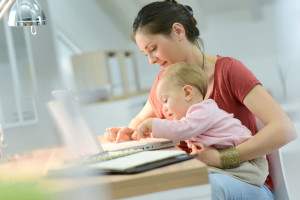47107742 - woman working from home with baby on lap