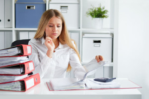 54644831 - beautiful business woman calculates tax at desk in office